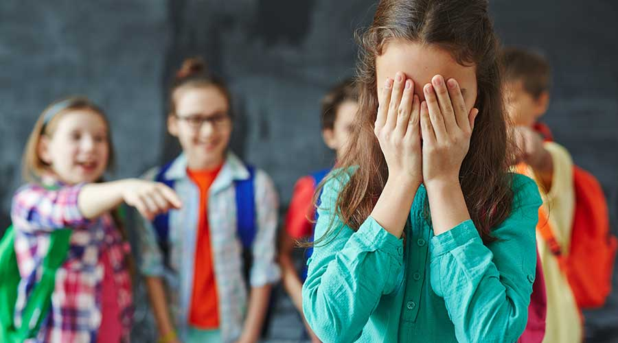 Schoolgirl crying on background of classmates teasing her