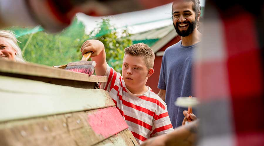 A youth helps paint the hen hut at the farm.