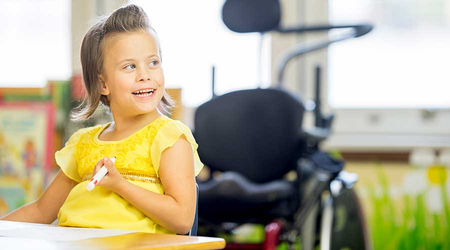 A happy little girl with cerebral palsy is sitting at a desk at an elementary school and is coloring a picture with a marker.