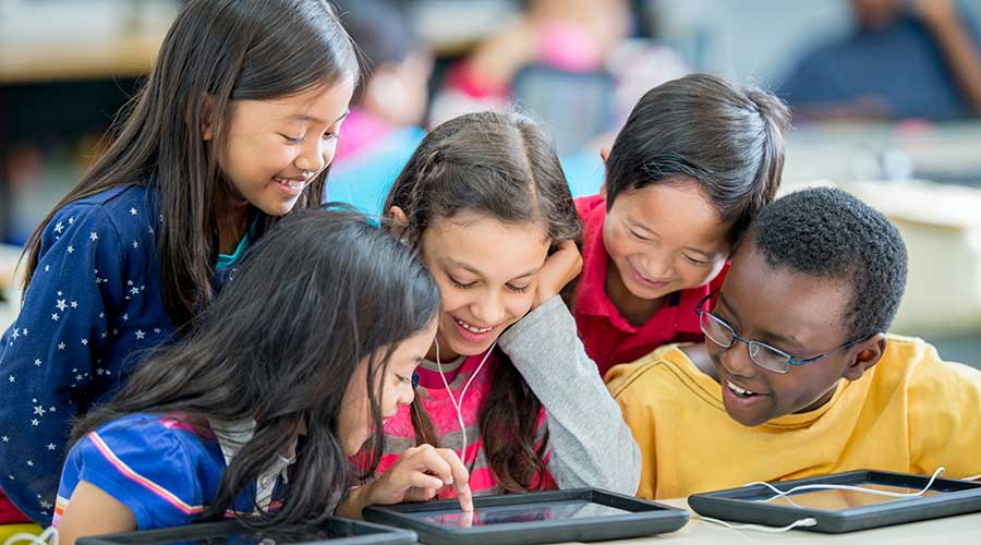 A multi-ethic group of elementary age children are sitting in the computer lab and are looking at a tablet together.