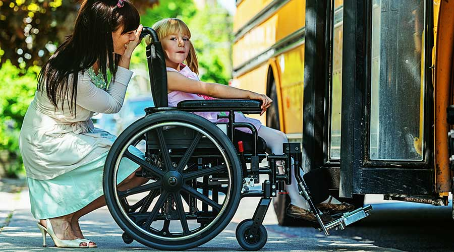 A mother talks with her daughter with a disability by her school bus.