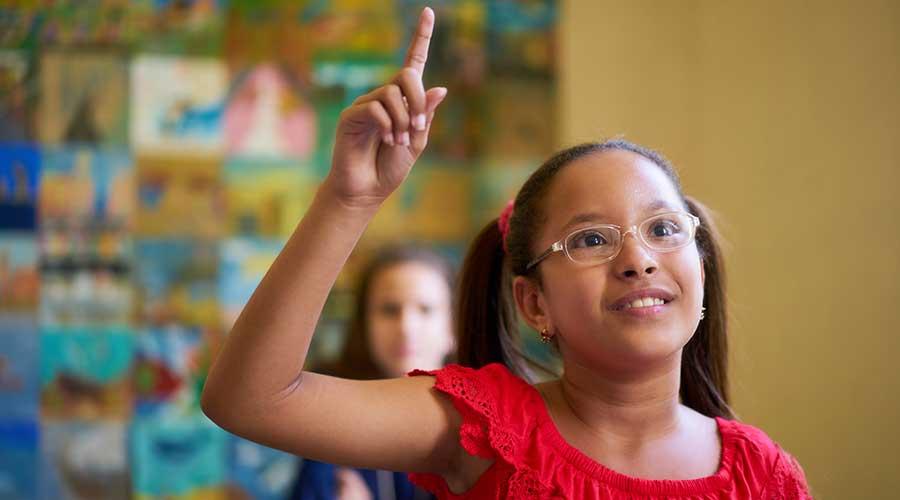 girl with eyeglasses raising hand