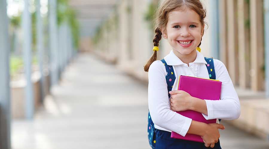 elementary school girl holding a textbook