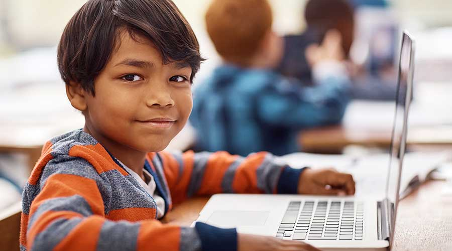 Portrait of an elementary school boy using a laptop while working in class