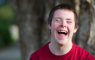 portrait of a boy youth with an intellectual disability laughing