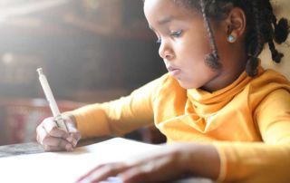 African American girl writing in notebook