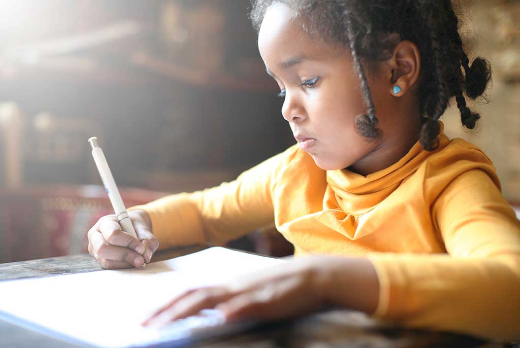 School child. African American girl writing in notebook.