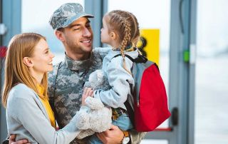 smiling father in military uniform holding in arms daughter near wife in airport