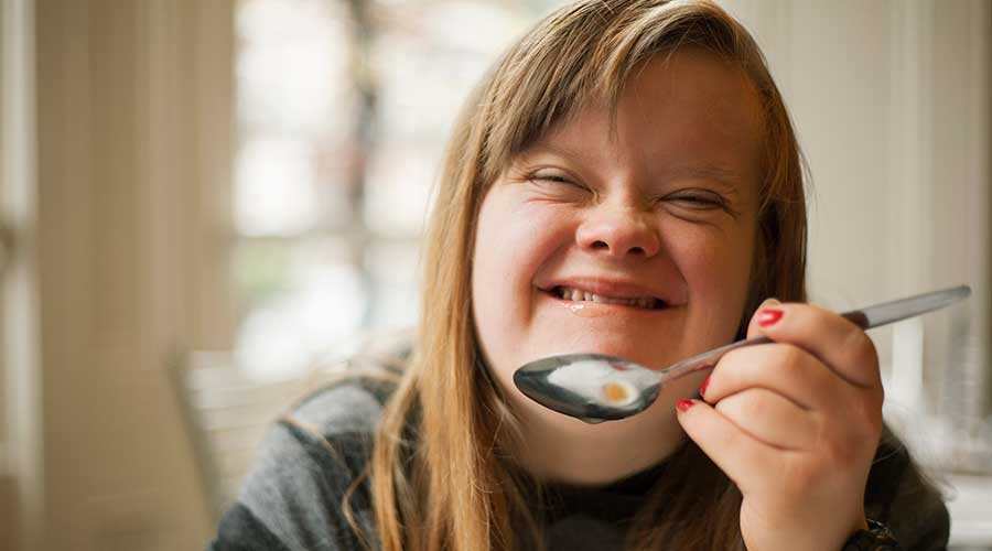 Young woman with Down Syndrome smiling and eating cereal