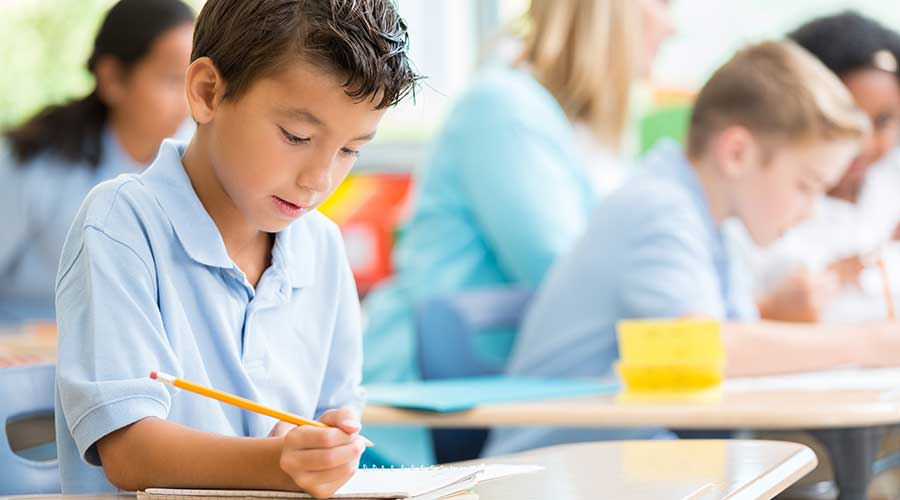 Hispanic male private school student confidently works on class assignment.