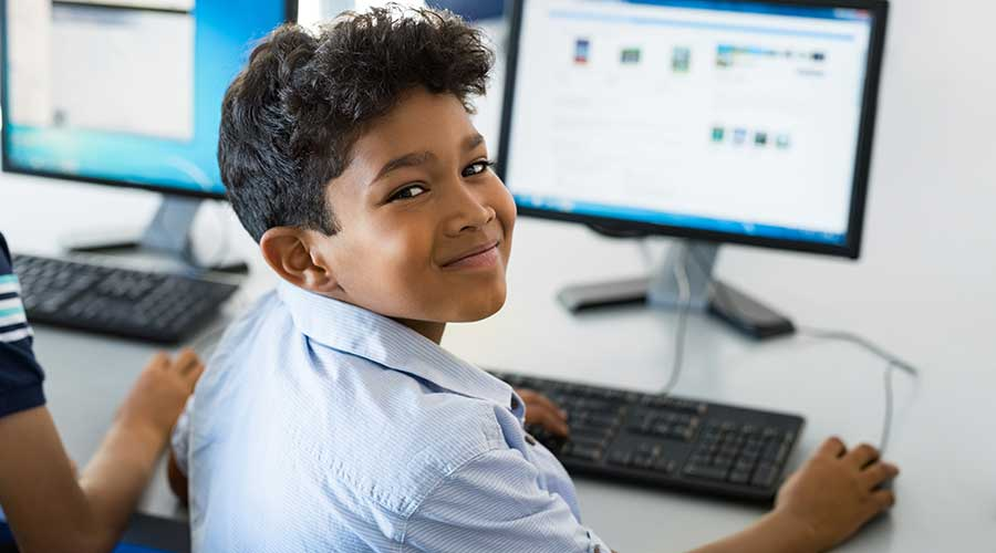 Young happy schoolboy using computer to search internet.